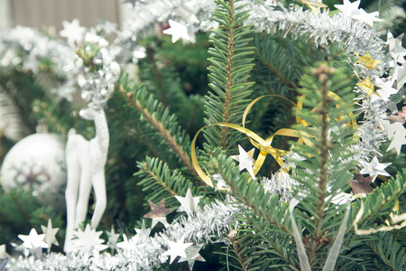 A white toy reindeer and a silver tinsel on a fir tree. Green Christmas or New Year background. Close up.