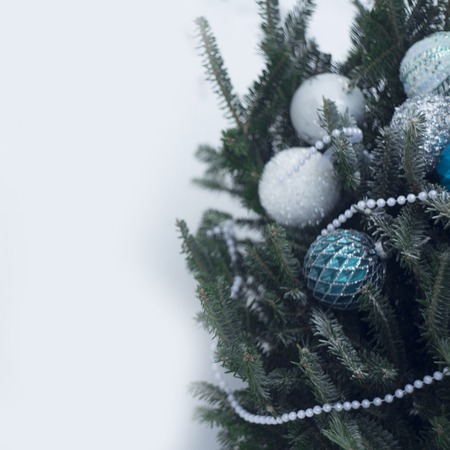 A Christmas tree decorated with minimalistic ornaments in white, silver and blue colors. White pearl beads on fir tree branches. Branches covered with frost. Christmas or New Year background.