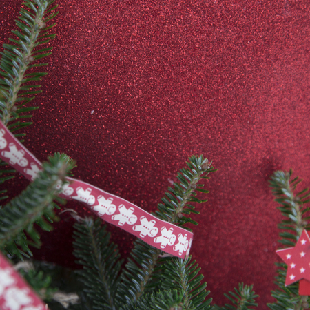 Red glitter Christmas background with fir tree branch and a red ribbon with a pattern. Close up Stock Photo