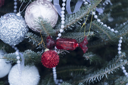 A festive mood with beautifully decorated Christas tree. White, Silver and red baubles and beads on fir tree branches covered with frost. Close up.