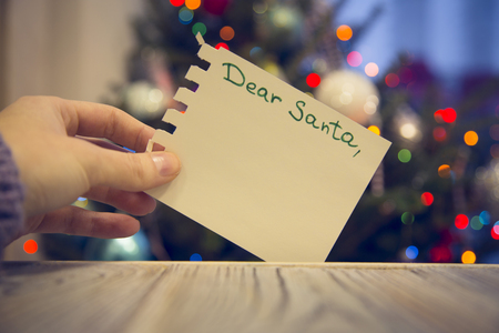 A hand holding a paper with Dear Santa inscription on a wooden table against decorated Christmas tree with colorful fairy lights. Blurred bokeh background. Close up.Mock up for display of product