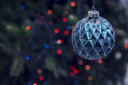 A New Year faceted blue bauble with silver glitter against dark blurred Christmas tree. Dark colorful red and blue bokeh