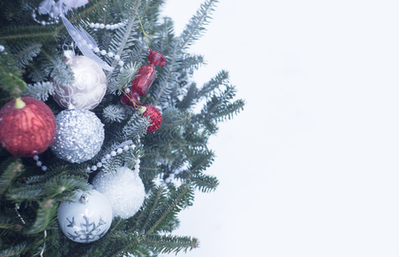 A festive mood with beautifully decorated Christas tree against white background. White, silver and red balls, white beads and ribbons on fir tree branches covered with frost.Cristmas or New Year background.