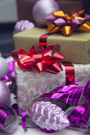 Gift boxes with bright metallic bows, Christmas-tree balls, ribbons and a pine cone in purple and lilac colors. Close up Stock Photo