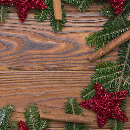 A cute Christmas frame made of natural fir tree branches, red stars, and cinnamon sticks on a rustic wooden table. Christmas or New Year background. Space for your text or product display. Square crop. Top view.