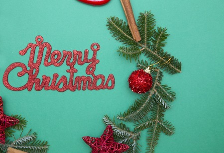 Red gleaming Merry Christmas inscription on a green one-color background with a frame of spruce branches, glitter red baubles. Top view. Stock Photo