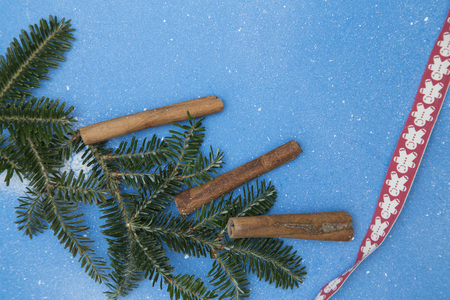 Blue spotted festive background with spruce branches, cinnamon sticksand a red ribbon. Space for your text or image. Top view. Square crop