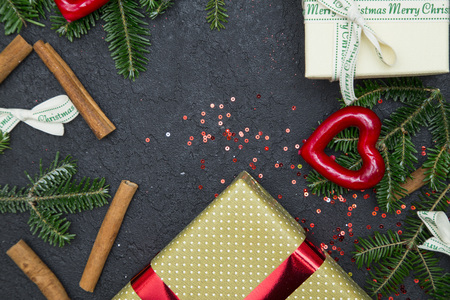 A festive frame of gift boxes tied with ribbons, spruce branches, sequins and cinnamon sticks.Dark concrete Christmas or New Year background. Top view. Stock Photo