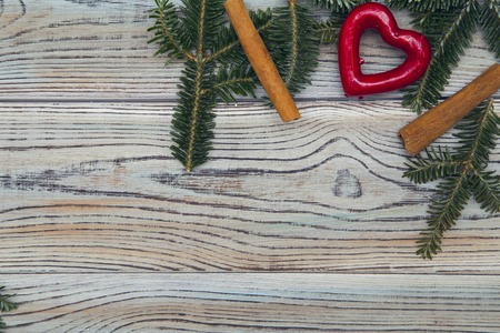 Light wooden shabby background for Christmas or New Year with a corner frame of spruce branches,cinnamon sticks and a red heart. Space for your text or product display. Top view. Close up