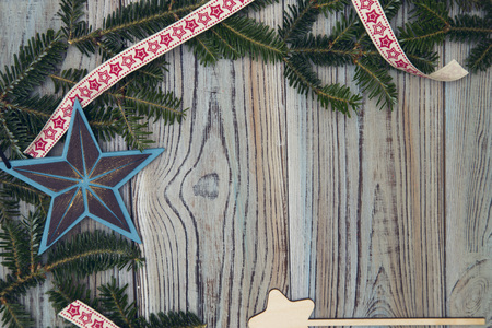 A frame of spruce branches, patterned ribbon and Christmas-tree and toy stars on a light wooden shabby background. Space for your text or product display. Top view. Close up