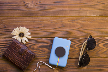 Packing luggage for a trip. A leather wallet, a flower, camera and black sunglasses on a rustic wooden background. Space for a text or product display, top view.