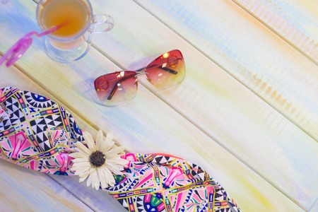 Enjoy time at the seaside. A swim suit, sunglasses and a fruit cocktail on a light colored wooden table.Tourism concept background, top view. Space for a text or product display. Stock Photo