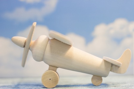 Travel concept. Fly abroad. A wooden toy airplane on a sky image background. Close up Archivio Fotografico