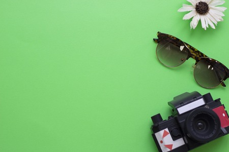 Green tourism concept background with flower, camera and sunglasses, top view. Space for a text or product display. Stock Photo