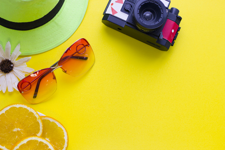 Bright yellow one-color background with a vintage camera, sunglasses and slices of orange, top view. Travel or tourism concept. Space for a text or product display.