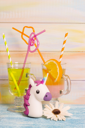 Romantiche vacanze estive. Cocktail esotici con cannucce colorate e un unicorno giocattolo. Sfondo in legno chiaro. Concetto di viaggio o turismo Archivio Fotografico - 92016786