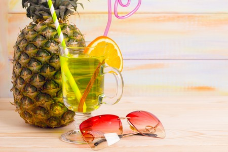 Enjoy a taste of fresh fruit at the beach. An exotic green cocktail, a fresh pineapple and pink sunglasses. Close up. Light colored wooden background. Travel and vacation concept. Banco de Imagens