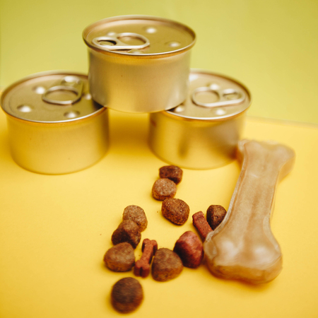 Feeding your pet friend. Tin cans of pet food and a chew bone on a bright one-color yellow background, close up, square crop. Pet care and veterinary concept. Spase for your text or image.