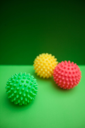 Colored rubber squaky ball toys for pets on a bright one-color green background. Pet care and veterinary concept. Spase for your text or image.