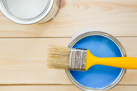 Renowating an appartment. A tin can of blue oil paint with a brush and can of white paint on a light uncolored wooden background. Close up. Top view. Space for your text or pruduct display. Stock Photo