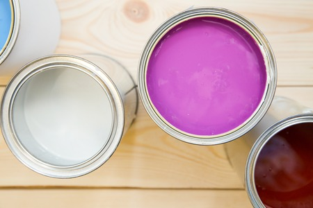 Painting new appartment. Tin cans of fuchsia, white and brown, oil paint on a light uncolored wooden background. Close up. Top view. Space for your text or pruduct display. Stock Photo