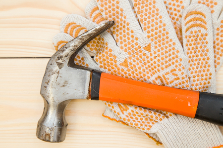 Repairing and construction concept. Tools for house repair- a hammer and a pair of protective work gloves on a light uncolored wooden background, close up. Top view. Space for your text or pruduct display. Stock Photo