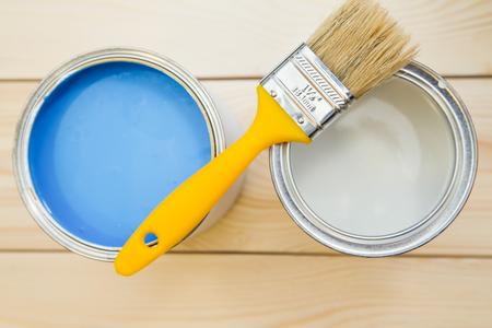 Reparación en una casa. Latas de pintura al óleo azul y blanca con un pincel amarillo y una lata de pintura blanca sobre un fondo de madera incoloro luz. De cerca. Vista superior. Espacio para su texto o pantalla de pruduct. Foto de archivo