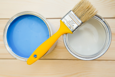 Repair in a house. Tin cans of blue and white oil paint with a yellow brush and can of white paint on a light uncolored wooden background. Close up. Top view. Space for your text or pruduct display.