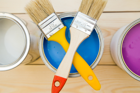 Ready to paint a house. A tin can of blue oil paint with crossed brushes on top,two cans of paint on each side, light uncolored wooden background. Close up. Top view. Space for your text or pruduct display.