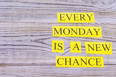 Every monday is a new chance printed on yellow paper inscription. Light wooden background.