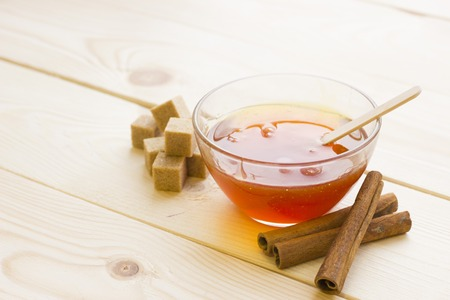 Sugaring essentials- A bowl of honey, brown sugar cubes and cinnamon sticsks. Light wooden background, Spa and body care concept.