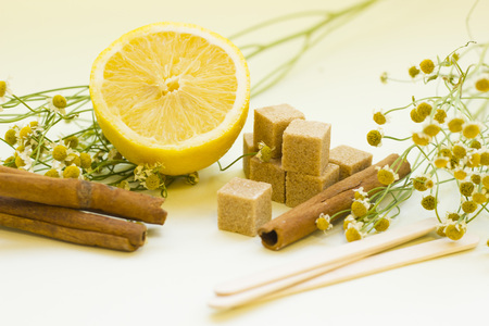 Natural ingridients for spa procedures- medical camomile, cinnamon, lemon, brown sugar and wooden sticks. Skin and hair treatment. Stock Photo
