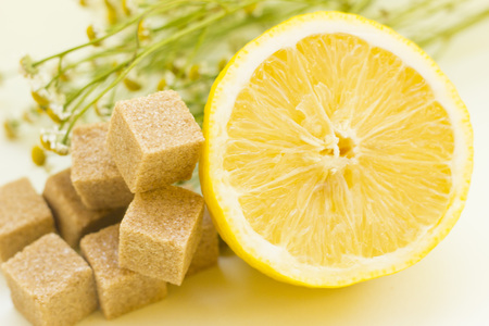 Concept for medical care, spa, beauty, healthy diet. A half of lemon, herbs and brown sugar cubes, light background. Close up.