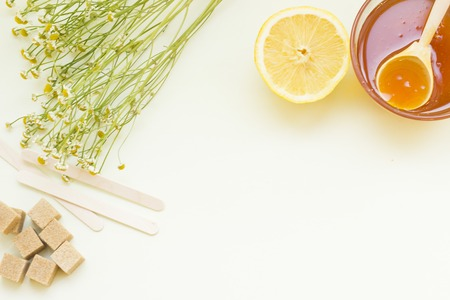 Background with a frame of natural ingredients for beauty and health- a bowl of honey with a wooden spoon, lemon, camomile, brown sugar cubes and wooden sticks. Space for your text or image