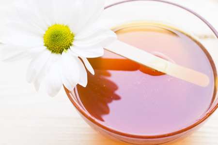 Spa and body care background. Mask and body massage- a bowl of natural fragrant honey and a camomile flower, close up. Stock Photo