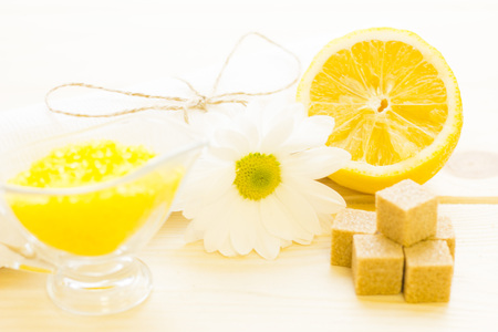 Spa therapy, body care, skin care concept.A white towel tied with a thread, camomile flower, a bowl of camomile bath salt, a lemon and sugar cubes, close up. A space for your text or product display.