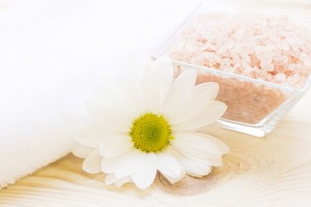 Spa and body care background. Relaxing bath- a square bowl of rose bath salt, a camomile flower and a white towel on a wooden table. Close up. A space for your text or product display. 스톡 콘텐츠
