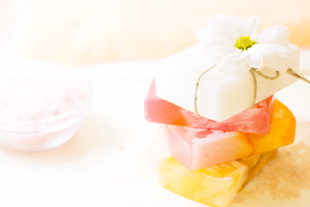 Enjoy fruit and flower fragrances in the bath. A pile of bars of homemade moisturizing soap with a fresh cut flower. Close up. Space for a text or product display.