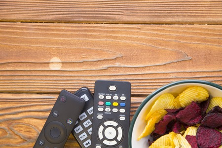 Weekend, leisure, hobby concept. A wooden background with tv remote controls and a bowl of potato and beetroot chips. Space for your inscription or image.