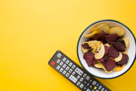 Weekend, hobby and leisure concept. A one-color yellow background with bowl of potato and beetroot chips and a tv remote control. Space for your text or image. Stock Photo
