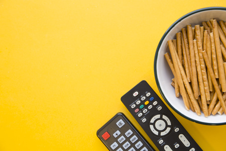 Weekend, hobby and leisure concept. A one-color yellow background with a bowl of salty bread sticks and two tv remote controls. Space for your text or image.