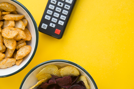 Entertaining at home. Weekend, hobby and leisure concept. A bowl of salty croutons and potato and beetroot chips and a remote control on a bright one-color yellow background. Stock Photo