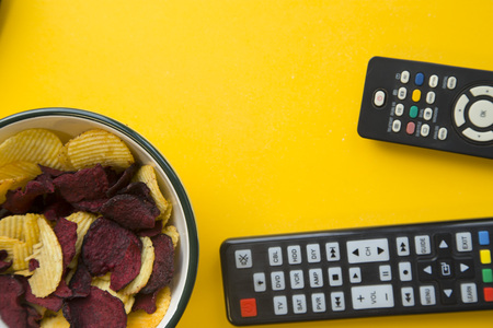 Relaxing in front of the tv. Weekend, hobby and leisure concept. A bowl of potato and beetroot chips and two remote controls on a bright yellow background.