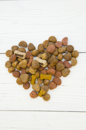 Pet care, veterinary concept. Love yor pet. A heart made of dry dog food. Close up. White wooden background. Vertical orientation.
