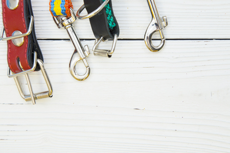 Take your outside. Stainless steel carbines and clips of leashes and collars on a white wooden background. Space for a text or image Stock Photo