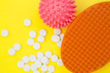 Pet care items set- a rubber brush, a rubber squeaky ball and scattered pet vitamins, close up. Stock Photo