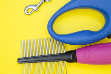 Pet care concept. A tape leash with a clipper and a pet stainless steel brush on a bright yellow background