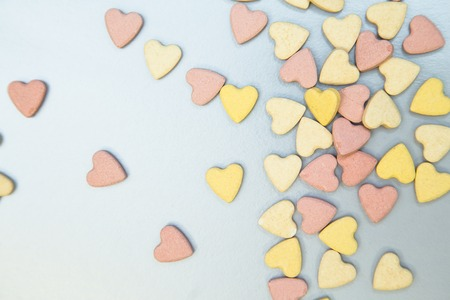 Veterinary and curing animals. A white background with scattered yellow and pink pills for pets in a shape of heart. Space for your text or product display. Stock Photo