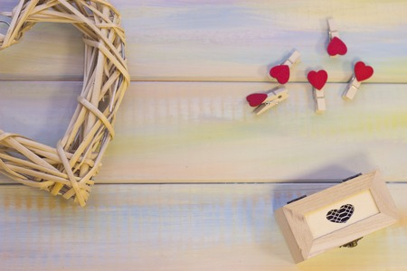 Natural wicker wreath in a shape of heart, a wooden box and heart-pins on a light backgound. Top view. St. Valentines, anniversary, wedding, mothers day concept. Stock Photo