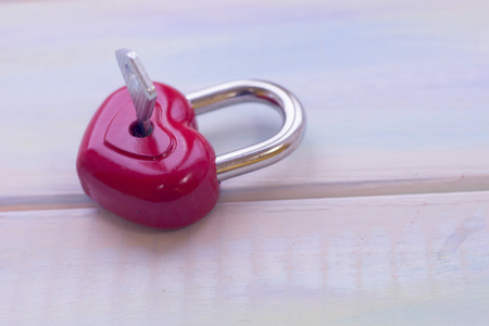 A locked red heart shaped lock with a key stuck on a light wooden background. St. Valentines, anniversary, wedding concept with copy space. Space for your text or product display. Stock Photo